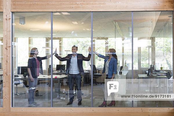 Team von drei Geschäftsleuten am Arbeitsplatz im modernen Büro
