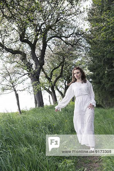 Junge Frau im weißen Kleid  die auf dem Fußweg geht.