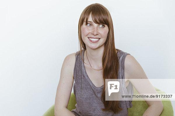 Porträt einer lächelnden Frau  die auf einem weichen Stuhl vor weißem Hintergrund sitzt.