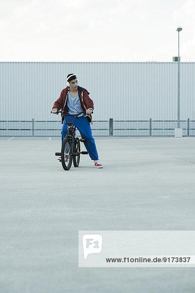 Junge mit BMX-Bike und Kopfhörer auf Parkebene