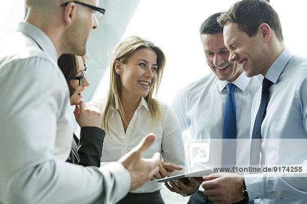 Geschäftsleute im Büro mit Frau mit digitalem Tablett