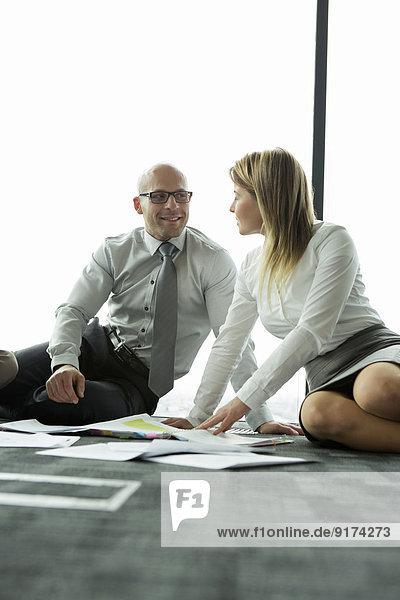 Geschäftsmann und Geschäftsfrau sitzen auf dem Boden und diskutieren über Papiere.