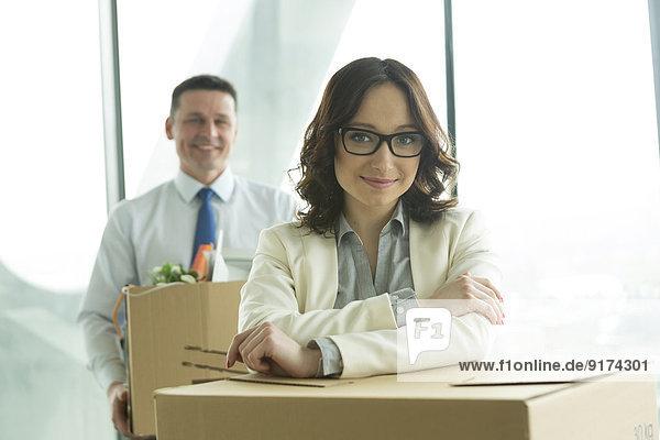 Geschäftsmann und Geschäftsfrau im Büro mit Pappkartons