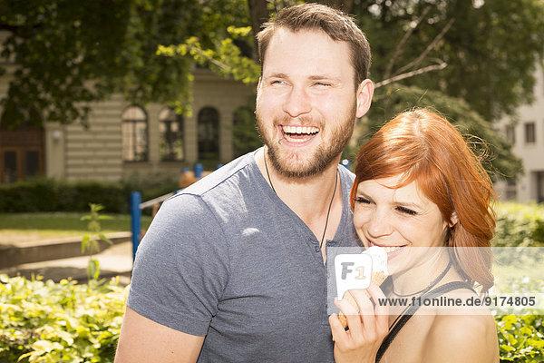 Deutschland  Bayern  München  Portrait eines glücklichen jungen Paares mit Eistüte