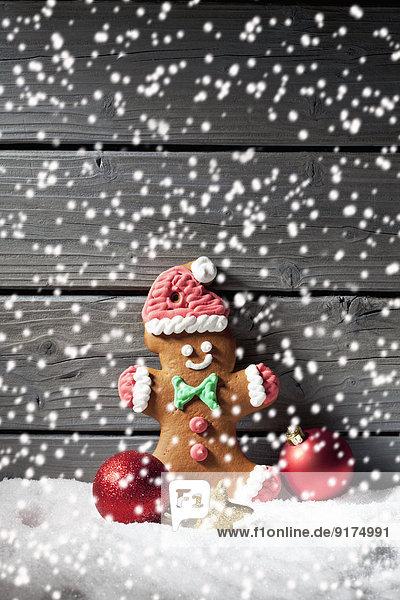 Lebkuchenmann und Weihnachtsblasen mit kräuselndem Kunstschnee davor