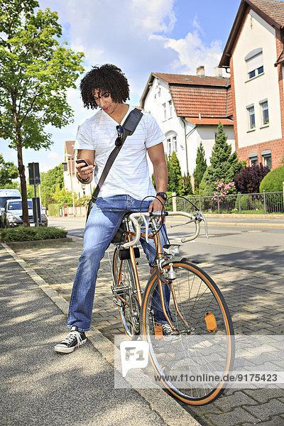 Ein junger Student sitzt auf einem Fahrrad und schaut auf sein Smartphone.