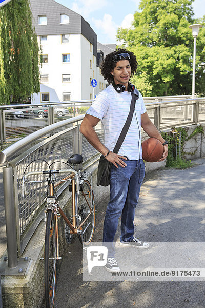 Junger männlicher Schüler mit Basketball neben seinem Rennrad