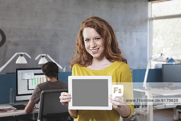 Porträt eines lächelnden Mannes mit Tablet-Computer im Büro