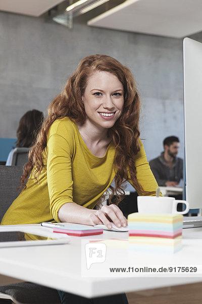 Porträt einer lächelnden Frau an ihrem Arbeitsplatz im Großraumbüro