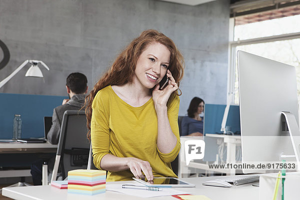 Porträt einer lächelnden Frau beim Telefonieren mit dem Smartphone am Arbeitsplatz im Großraumbüro