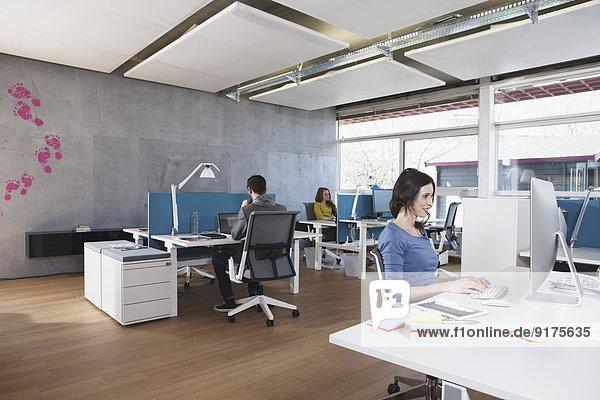 Drei Kollegen im modernen Großraumbüro