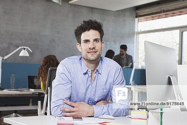 Porträt eines lächelnden Mannes an seinem Arbeitsplatz im Büro