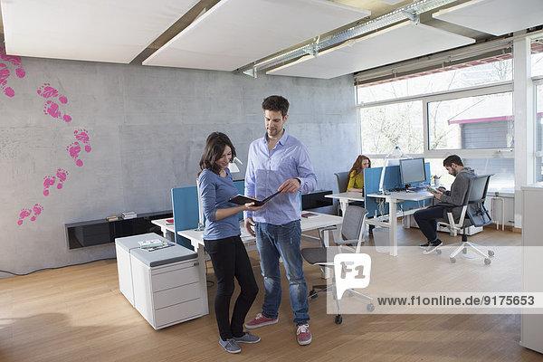 Vier Kollegen im modernen Großraumbüro