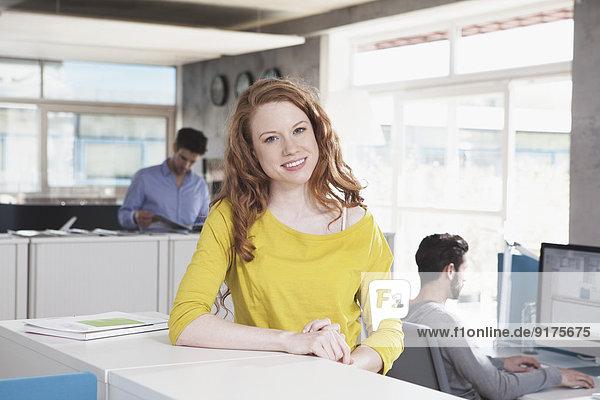 Porträt einer lächelnden Frau im Großraumbüro