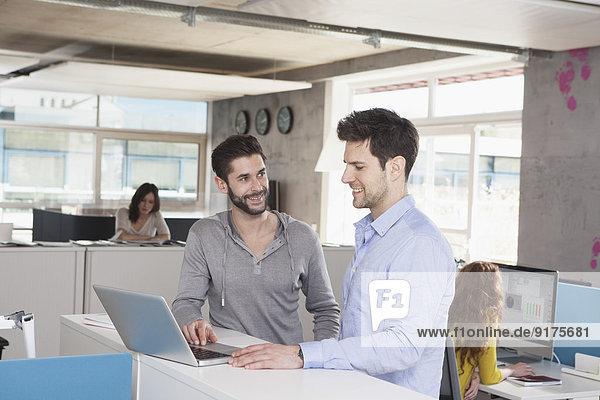 Zwei Kollegen mit Laptop in einem Großraumbüro