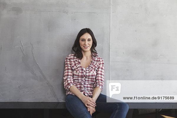 Porträt der lächelnden Frau vor grauer Wand