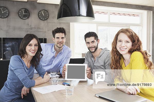 Gruppenbild von vier kreativen Menschen  die einen Tablet-Computer im Büro zeigen.