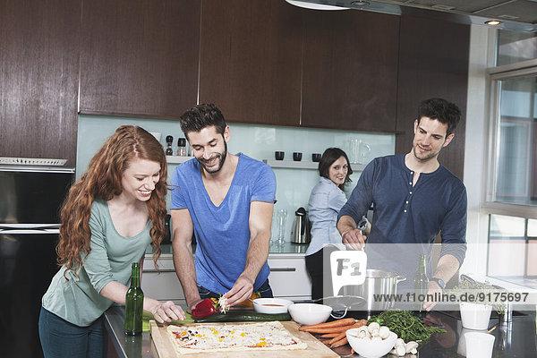 Porträt von vier Freunden beim gemeinsamen Kochen