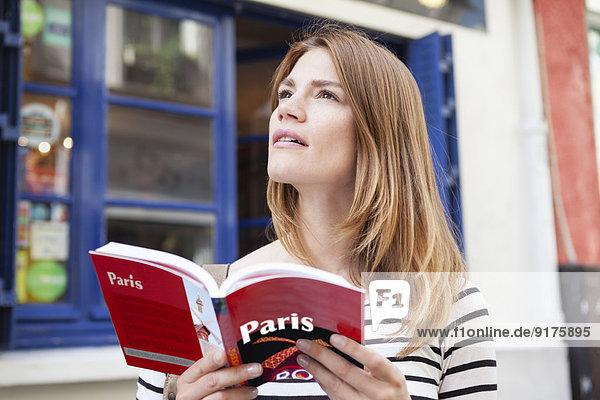 Frankreich  Paris  Portrait einer jungen Frau mit Reiseführer