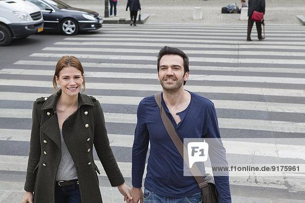Frankreich  Paris  Paar  das Hand in Hand auf dem Zebrastreifen läuft