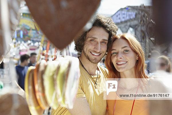 Glückliches junges Paar auf einem Jahrmarkt