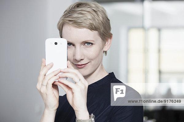 Deutschland  München  Geschäftsfrau im Büro  mit Smartphone