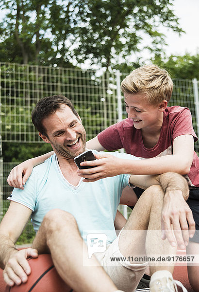 Germany  Mannheim  Father and son looking at smart phone