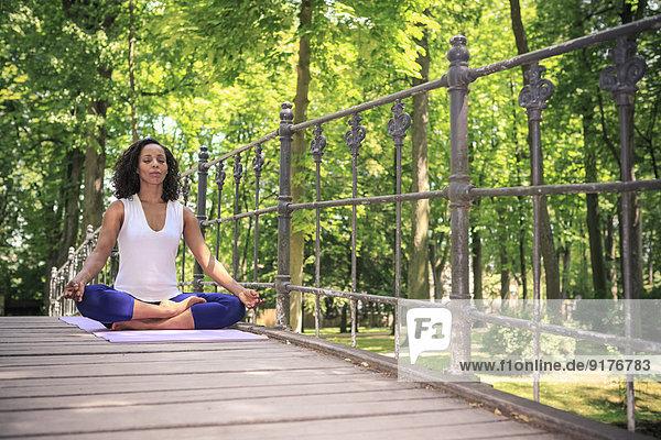 Frau macht Yoga-Übungen im Park