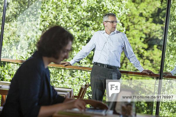 Geschäftsfrau mit Laptop im Restaurant mit Geschäftsmann auf dem Balkon