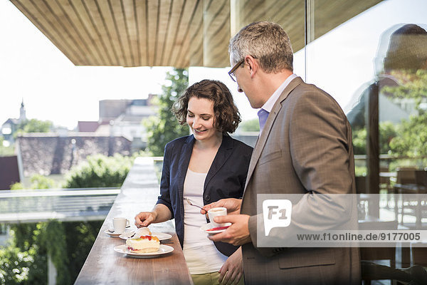 Geschäftsmann und Geschäftsfrau im Gespräch auf dem Balkon