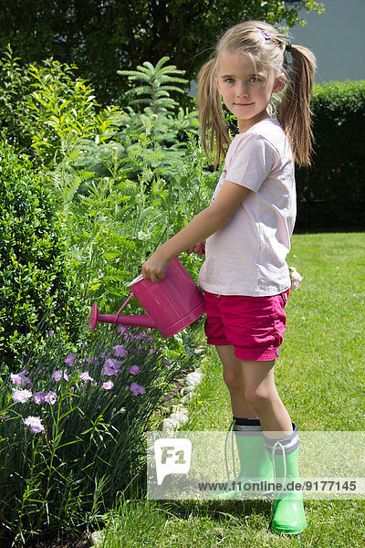 Portrait of little girl pouring plants with pink watering can in the garden
