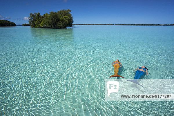 Palau  zwei junge Frauen in Meerjungfrau-Kostüm schwimmend in einer Lagune