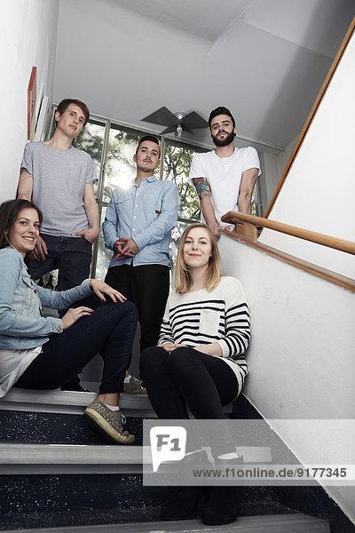 Gruppe selbstbewusster Kreativprofis im Treppenhaus