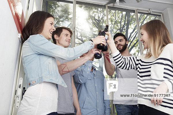 Gruppe von Kreativen  die im Treppenhaus Bier trinken