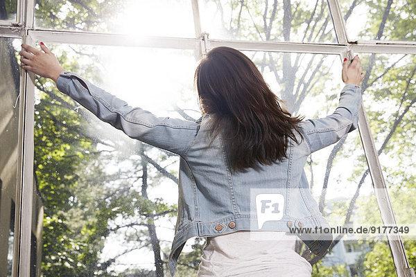 Frau am Fenster mit Blick nach draußen