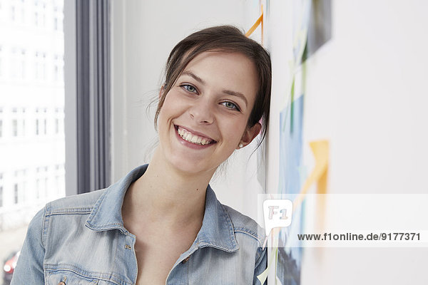 Smiling woman leaning against wall with adhesive notes