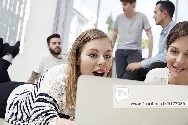 Gruppe von Kreativprofis mit Laptop am Boden