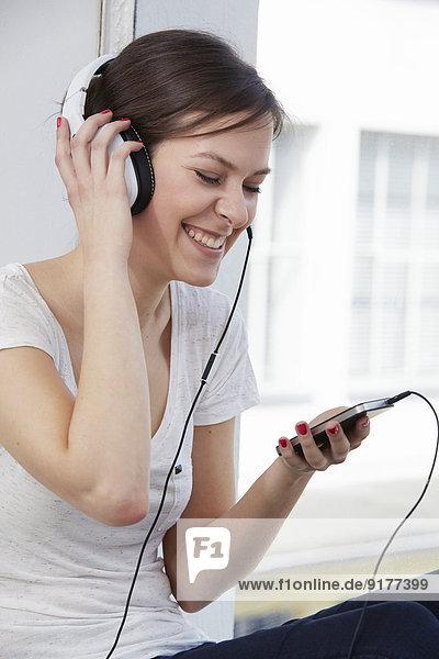 Junge Frau mit Kopfhörer am Fenster