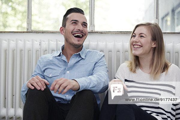 Glücklicher Mann und Frau auf dem Boden sitzend