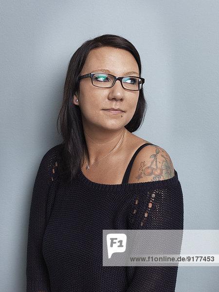 Bildnis der brünetten Frau mit Brille vor grauem Hintergrund