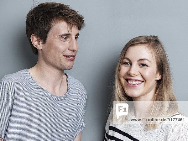 Porträt des smikling Paares vor grauem Hintergrund