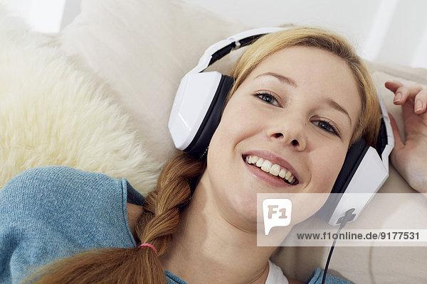 Porträt einer Teenagerin beim Musikhören mit Kopfhörern zu Hause