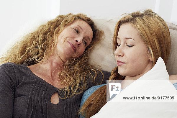Porträt von Mutter und Tochter auf der Couch zu Hause