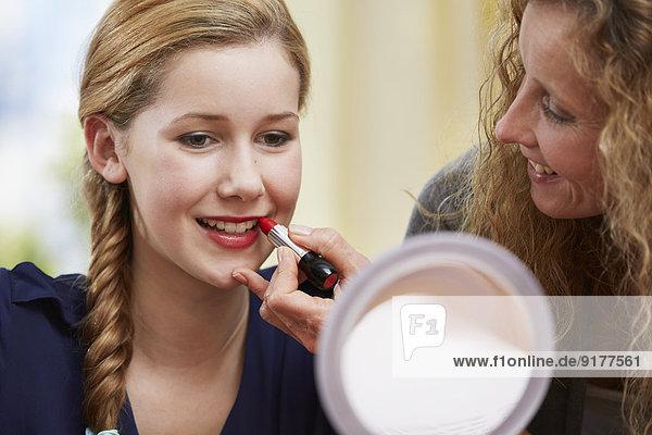 Mutter zeigt ihrer Tochter  wie man Lippenstift benutzt.