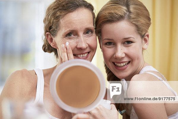 Portrait von Mutter und Tochter Wärme zum Kopf mit Handspiegel