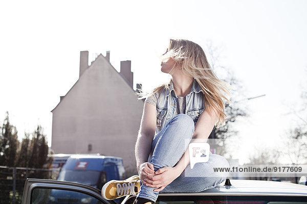 Junge Frau auf dem Autodach sitzend Junge Frau auf dem Autodach sitzend