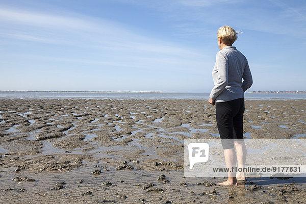 Germany  Lower Saxony  Nessmersiel  woman looking at wadden sea