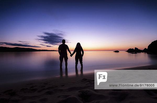 Spain  Menorca  Couple watching sunset at Playa de Cavalleria