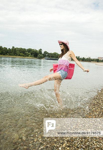 Junge Frau mit Hut und Tasche hat Spaß am Rheinufer