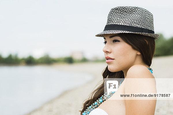 Porträt einer jungen Frau mit Hut am Strand